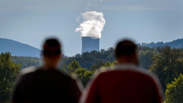 Deux homme font face à la tour de refroidissement de la centrale nucléaire de Goesgen de la ville suisse d'Aarau.
