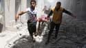 Des hommes syriens évacuant un corps après des bombardements sur Alep, le 29 avril 2016.