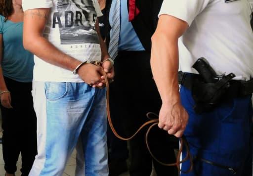 Un des quatre suspects est conduit par un policier hongrois au tribunal de Kecskemét, le 29 août 2015 en Hongrie