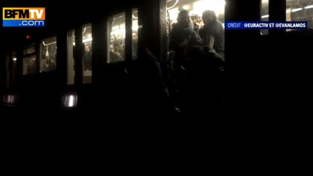 Les passagers bloqués dans le métro tentent d'évacuer une rame plongée dans l'obscurité, mardi.
