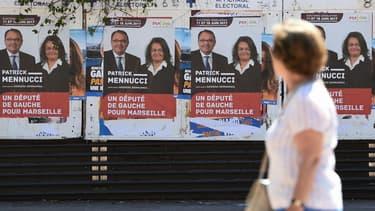 Une femme passe devant les affiches de campagne de Patrick Mennucci, candidat socialiste battus aux élections législatives, le 28 mai 2017 à Marseille.