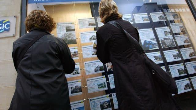 Des passants lisant les annonces d'une agence immobilière