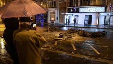 Des passants prennent en photo des scooters brûlés au milieu des rues de Paris le 8 décembre 2018