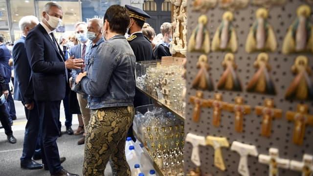 Bruno Le Maire dans une boutique de souvenirs près du sanctuaire de Notre-Dame de Lourdes, le 10 août 2020, lors de sa visite pour soutenir les professionnels du secteur du tourisme