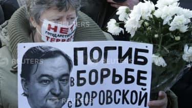 Une femme brandit le portrait de Sergueï Magnitski, pendant une manifestation clandestine à Moscou le 15 décembre 2012 contre le président Vladimir Poutine.