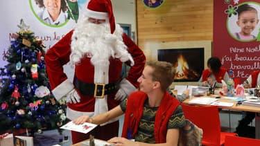 Le Père Noël à côté d'un employé de La Poste