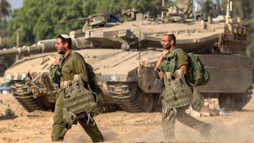 Des soldats israéliens passent devant un tank Merkava à la frontière sud de la bande de Gaza, le 1er août 2014.