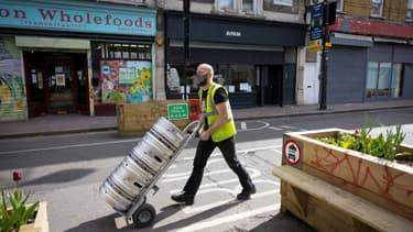 Un homme livre de la bière dans un pub de Londres en prévision de l'allègement des restrictions sanitaires le 9 avril 2021