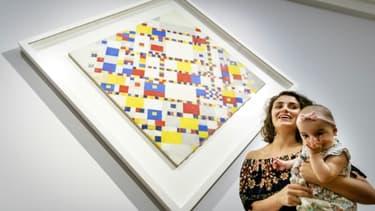 Une femme porte un bébé choisi parmi un groupe de 400, pour admirer en exclusivité des oeuvres de Piet Mondrian, le 11 juillet 2017 au Gemeentemuseum de La Haye