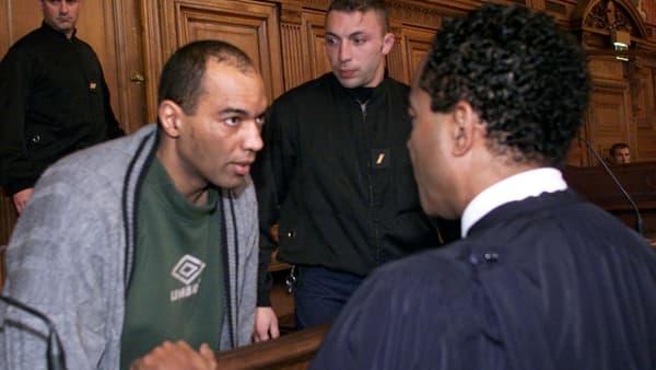Guy Georges discute avec son avocat, le 19 mars 2001, lors de son procès.