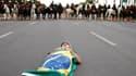 Un manifestant se couche, enveloppé dans un drapeau brésilien, en travers de la route près du stade national Mane Garrincha, à Brasilia.