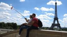 Un couple de touristes en train de se prendre en selfie devant la Tour Eiffel à Paris le 21 mai 2017 (Photo d'illustration).