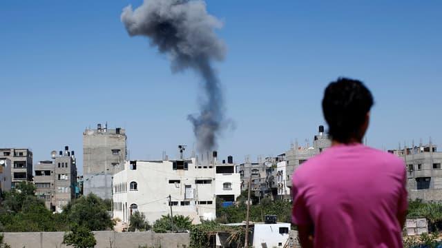 Un Palestinien regarde la fumée s'échappant d'un immeuble après une frappe israélienne sur Gaza, le 9 juillet 2014.