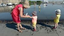 Une femme en train d'appliquer de la crème solaire à une enfant.