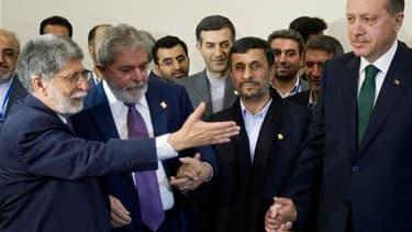 Le président brésilien Lula da Silva (2e à gauche) et son ministre des Affaires étrangères Celso Amorim (à gauche), main dans la main avec le président iranien Mahmoud Ahmadinejad et le Premier ministre turc Recep Tayyip Erdogan à Téhéran. L'Iran a signé