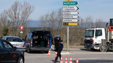 Des gendarmes bloquent l'accès à Trèbes, où Radouane Lakdim a pris plusieurs personnes en otages le 23 mars 2018.