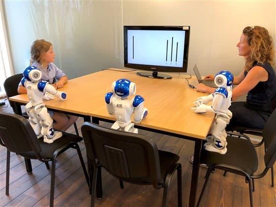 L'enfant entouré des robots pendant l'expérience