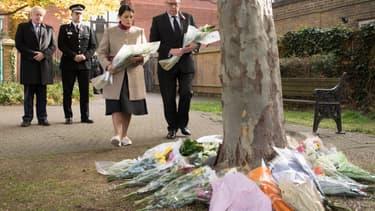 Le Premier ministre britannique Boris Johnson, le chef de la police de l'Essex et la secrétaire à l'Intérieur déposent des fleurs après la découverte des 39 corps dans un camion, le 28 octobre 2019