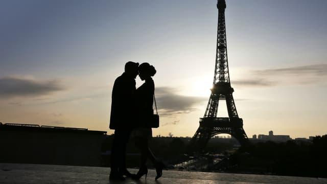 Un couple devant la tour Eiffel, à Paris (photo d'illustration)