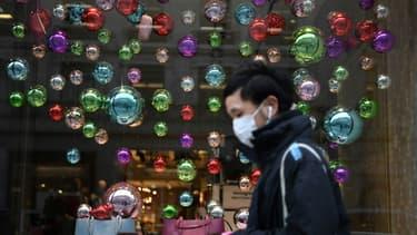 Image d'illustration - Un client masqué devant une vitrine de magasin