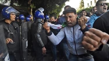 Les forces de sécurité algériennes entourent des manifestants qui organisent une manifestation anti-gouvernementale à Alger le jour de l'élection présidentielle. RYAD KRAMDI / AFP
