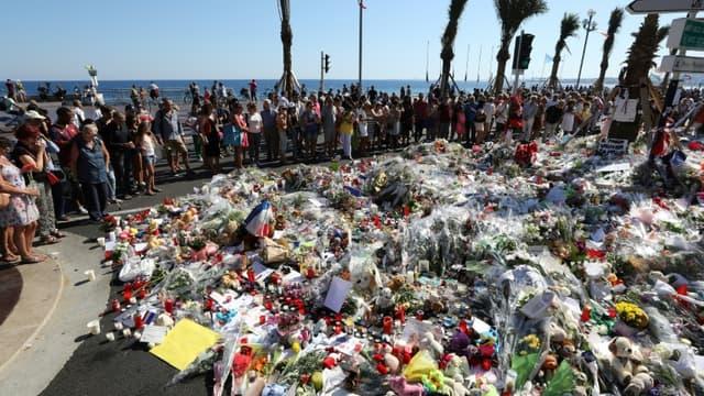 Des personnes déposent des fleurs et des messages à la mémoire des victimes, le 17 juillet 2016 à Nice, trois jours après un attentat qui a fait 86 morts le 14 juillet sur la Promenade des Anglais