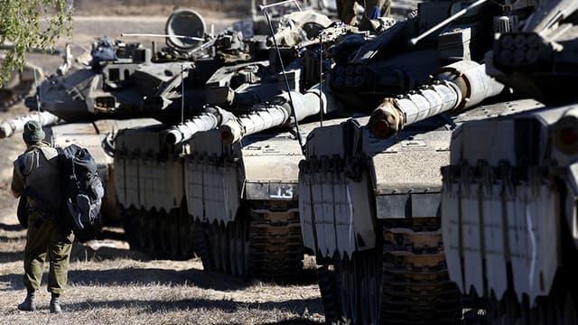 Un soldat israélien marche le long des tanks Merkava alignés sur la frontière.