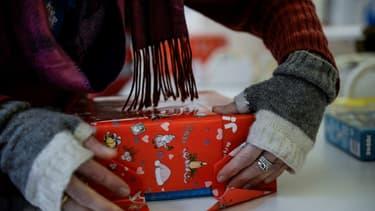 Image d'illustration - Dans un magasin de jouets à Paris, le 16 décembre 2019, une salariée en train d'emballer un cadeau de Noël.