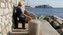L'épave du Costa Concordia, vue depuis le port du Giglio. Six mois après le naufrage du paquebot au large de la Toscane, une cérémonie a été organisée vendredi en mémoire des victimes sur la petite île du Giglio. Les cloches de l'église ont sonné à 21h42,