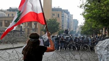 Une manifestante faire face à des forces de sécurité lors d'une manifestation à Beyrouth, le 8 août 2020