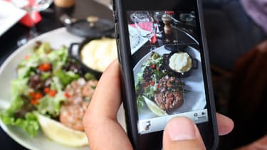 Image prise le 19 juin 2012, montrant un homme prenant en photo son plat dans un restaurant parisien.