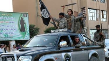 Une photo de propagande diffusée par le média jihadiste Welayat Raqa montre des membres du groupe Etat Islamique paradant dans une rue de Raqa, le 30 juin 2015 en Syrie