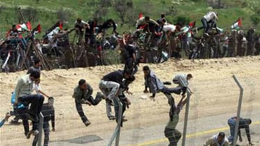 """Des manifestants syriens escaladent la barrière à la frontière entre Israël et la Syrie, lors d'un rassemblement à l'occasion de la """"Nakba"""" ou """"catastrophe"""" pour les Palestiniens, qui marque l'anniversaire de la création d'Israël. Des violences ont éclaté"""
