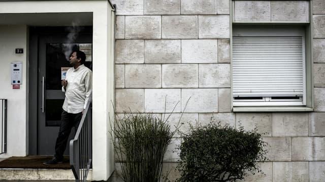 Un réfugié érythréen fume une cigarette à l'entrée de son appartement de la maison des réfugiés de Pouilly-en-Auxois, en Côte d'Or.