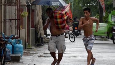 Des habitants mettent leurs biens à l'abri avant l'arrivée du typhon Mangkhut, le 14 septembre.