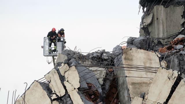 Les secouristes reconnaissent les décombres du viaduc Morandi.