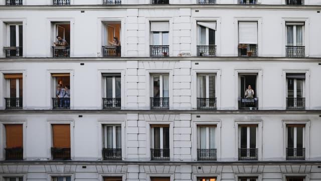 Des Français à leurs fenêtres pour applaudir les soignants en première ligne dans la lutte contre le Covid-19, le 30 mars 2020.