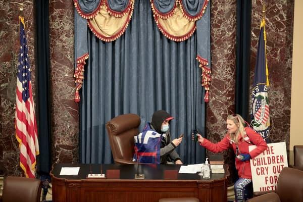 Un manifestant assis au micro de la chambre des Représentants ce mercredi, après être parvenu à entrer dans le Capitole.