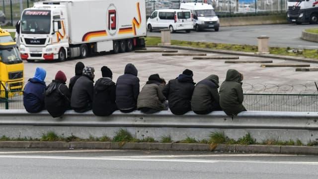 Des migrants sont assis sur une barrière près de la rocade du port de Calais le 30 mars 2018