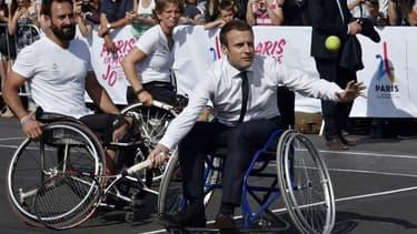 Emmanuel Macron s'essaye au tennis en fauteuil pour promouvoir la candidature de Paris aux Jeux Olympiques 2024, à Paris le 24 juin 2017.