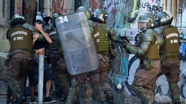 Des forces de police arrêtent un manifestant pendant une manifestation contre le gouvernement, à Santiago du Chili, le 16 novembre 2019
