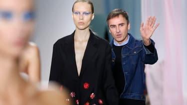 Raf Simons salue le public à la fin du défilé printemps-été 2013 de Dior, le 28 septembre