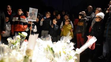 Des enfants et leurs parents rendent hommage au directeur assassiné, la semaine dernière.