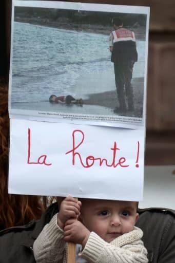 Un enfant tient une pancarte montrant la photo du petit garçon syrien découvert mort sur une plage turque, le 5 septembre 2015 lors d'une manifestation à Strasbourg