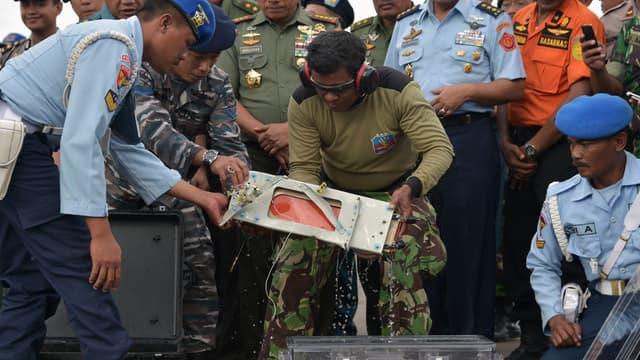 Des officiers enveloppent la boîte noire retrouvée dans un étui protecteur, le 12 janvier.
