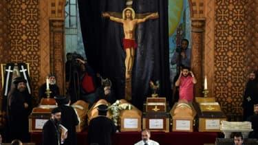 Des prêtres coptes près des cercueils des victimes de l'attentat de l'église Saint-Marc d'Alexandrie, le 10 avril 2017 au monastère de Mar Mina à Borg El-Arab, en Egypte