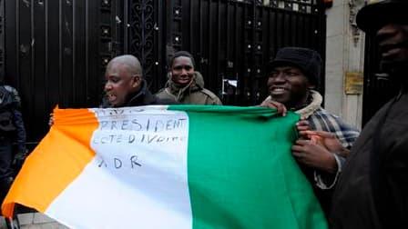"""Des partisans d'Alassane Ouattara déploient un drapeau ivoirien devant l'ambassade de Côte d'Ivoire à Paris. Des militants pro-Ouattara ont affirmé lundi avoir pénétré """"pacifiquement"""" dans l'ambassade pour protester contre le maintien au pouvoir du présid"""