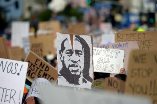 Des manifestants brandissent un portrait de George Floyd lors d'un rassemblement pour dénoncer le racisme et les violences policières, à Hollywood, le 7 juin 2020