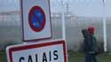 """Des migrants, portant des bagages, passent à côté un panneau marquant les limites de la ville de """"Calais"""", le 24 octobre 2016."""