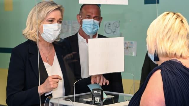 La président du Rassemblement National (RN) Marine Le Pen vote au 1er tour des régionales à Hénin-Beaumont en présence du maire de la ville Steeve Briois (d), le 20 juin 2021